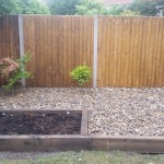 Sleeper border with plants and shingle and a vegetable patch
